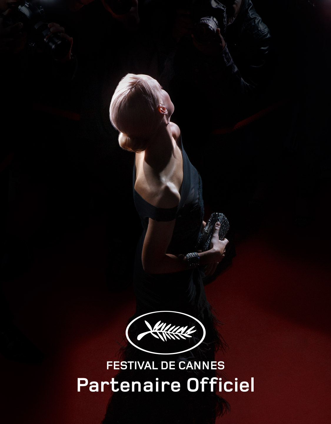 Actress smiling at photographs during Cannes Film Festival