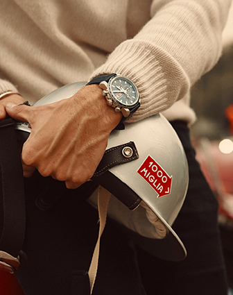 Close-up of a watch from the Mille Miglia Collection on a man's hand. He is holding a grey velvet as well.