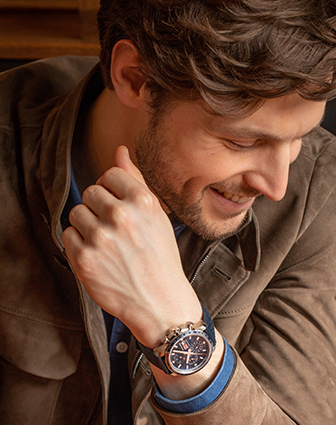 An elegant man wearing a watch from the Mille Miglia Collectio. He is looking down, smiling