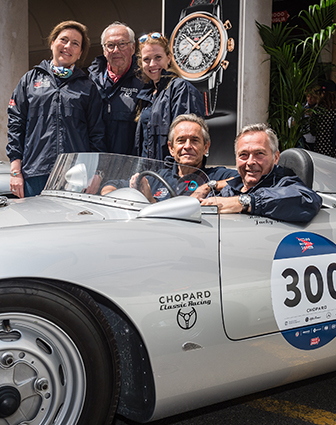 A family of racing experts, with two men sitting on a racing car and the three others standing behind the light gray racing car.