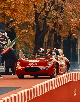 A red racing on a red racing road, with an autumn background, full of orange leaves