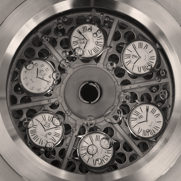 Close-up in black and white on watches immersed in water to test water resistance.