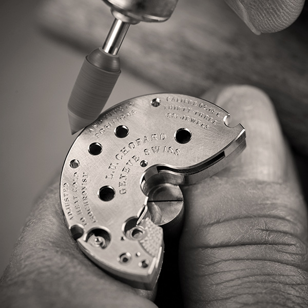 Close-up in black and white on the hand of a Chopard craftsman working on the decoration of the movement.