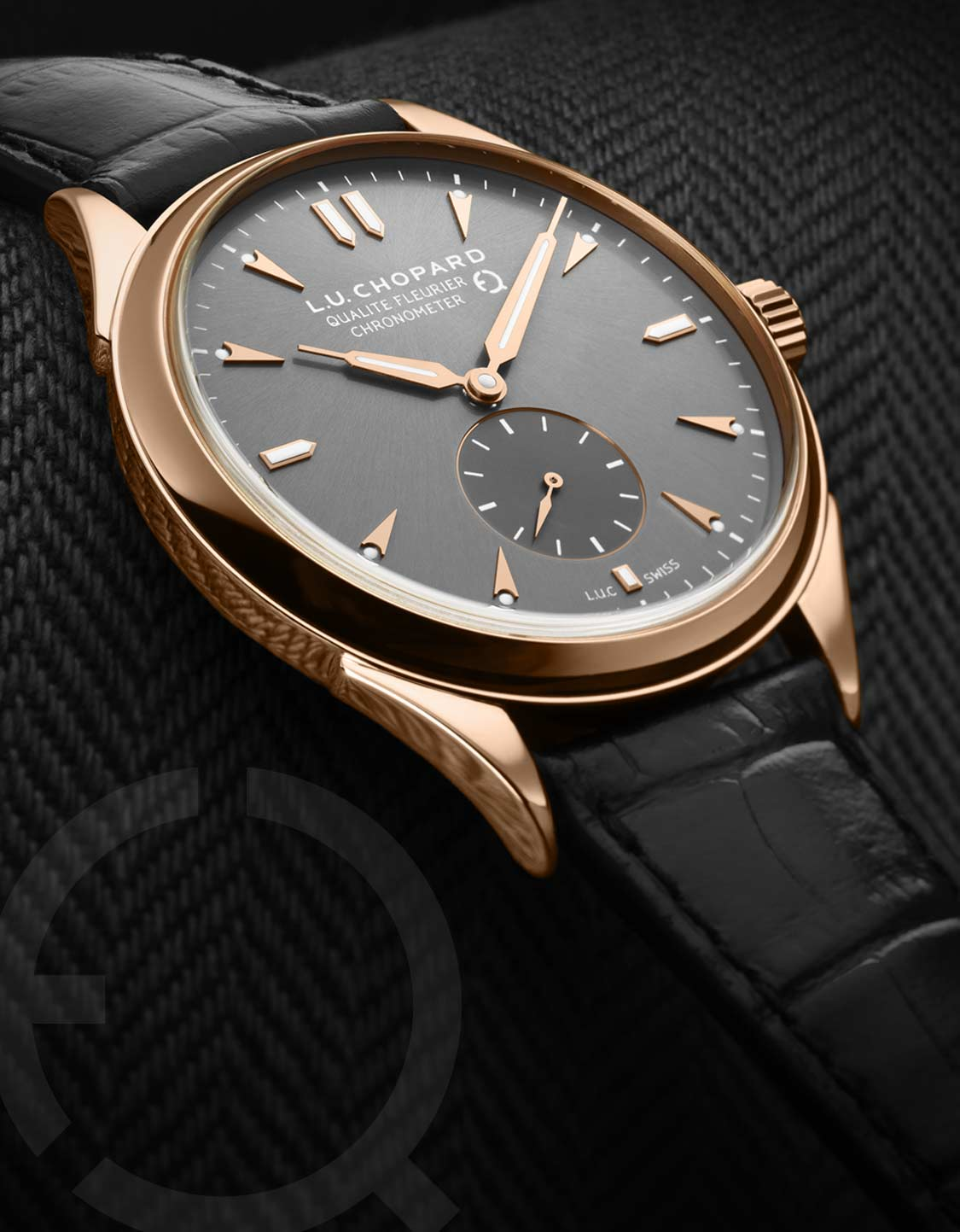 Close-up on the LUC Qualité Fleurier watch in rose gold with black dial and bracelet.
