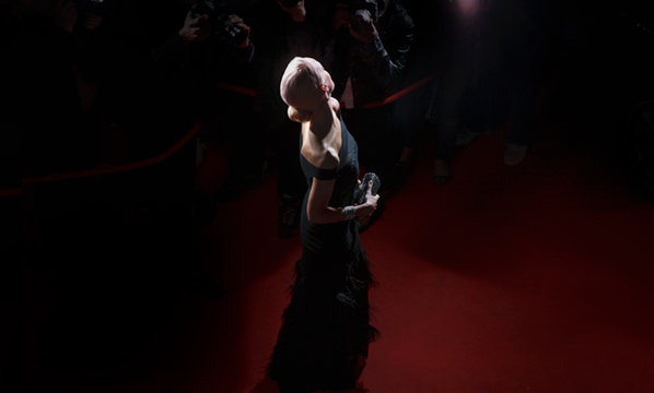 Woman shot by photographs as she walks on the red carpet during the Cannes Film Festival